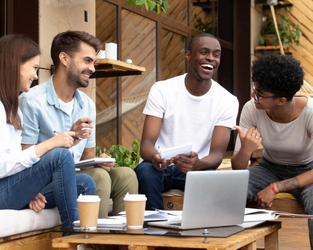 A group of four people smiling while working around a laptop outside of a cafe