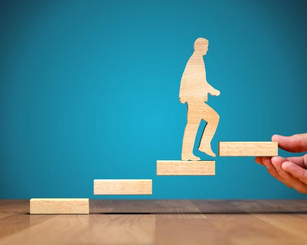 Wooden figure of a man walking up wooden block steps suspended in air