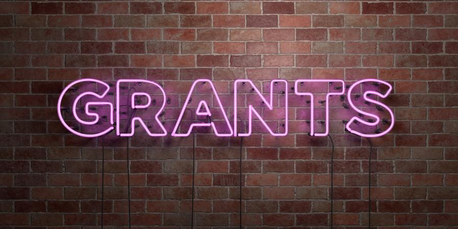 "pink fluorescent neon tube sign on brick wall reading ""Grants"""