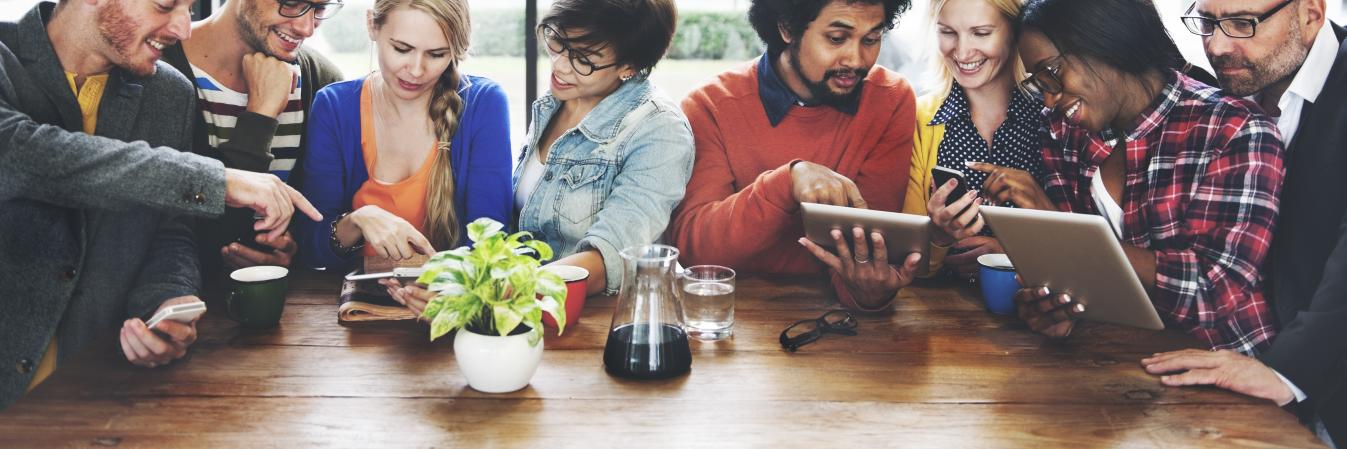 Group of people at table with tablets networking on social media